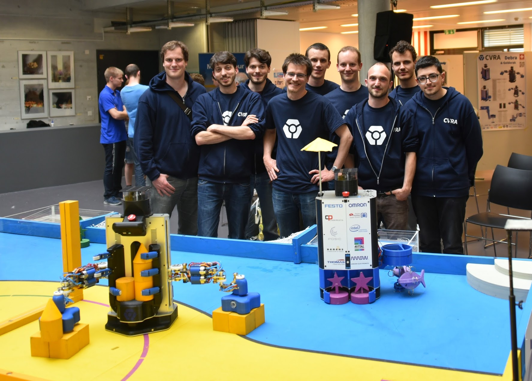 The team posing in front of the robots.
